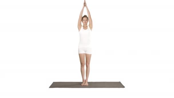 Atraktivní dívka stojící v rovnováze jóga póza Garudasana Mladá žena v Eagle jóga póza na bílém pozadí.