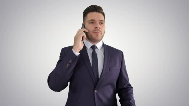 Serious worried businessman talking on cellphone on gradient background.