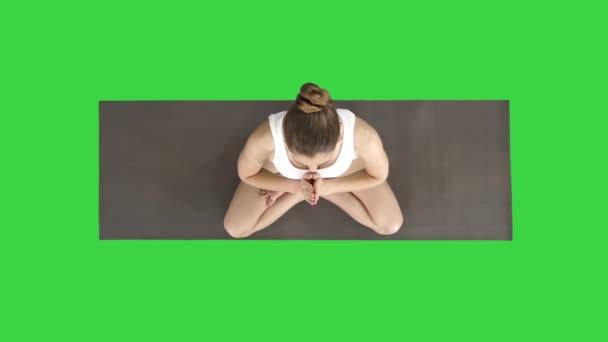 Mladá jogurtová žena, která cvičila jóga, dělá Namaste gesto v lotosové pozici, nosí bílé tričko na zelené obrazovce, Chroma Key.