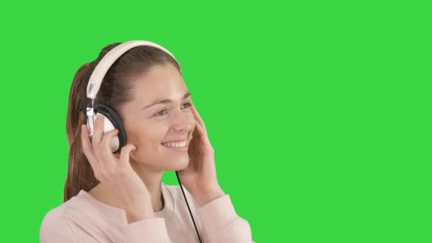 Mladá krásná žena ve světlých šatech užívajících hudbu na zelené obrazovce, klíč Chroma.
