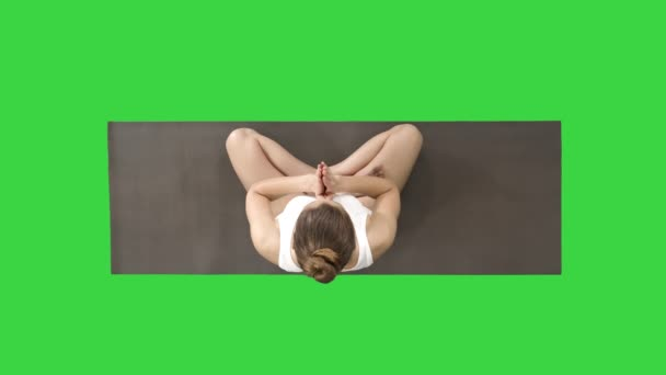 Young woman sitting in lotus pose and meditating on a Green Screen, Chroma Key.