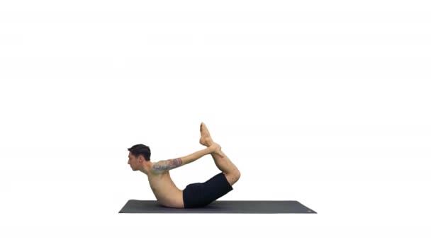 sportlicher muskulöser junger Yogi-Mann bei Rückenbeugeübungen, Dhanurasana, Bogenhaltung auf weißem Hintergrund.