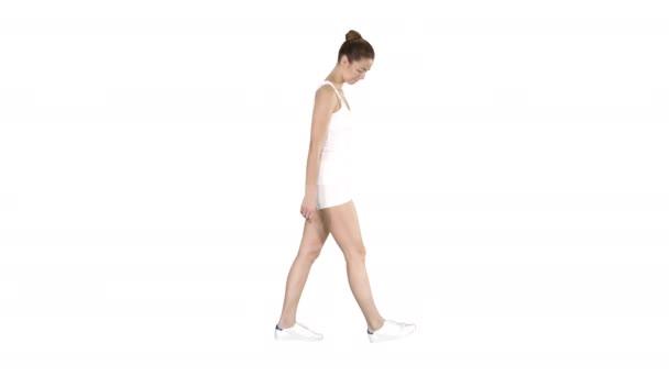 Mladá žena v sportovním oblečení procházka po bílém pozadí.
