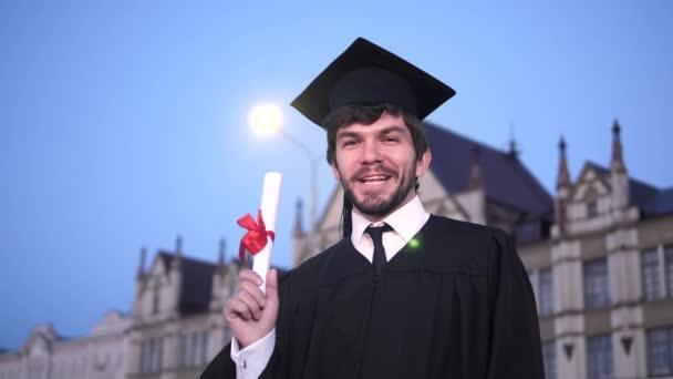 Chlápek v maturitní jednotce se usmívá a ukazuje diplom kameramana.