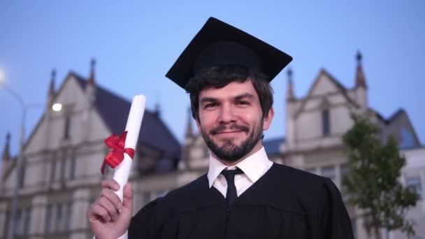 Kaukázusi boldog fiatal diplomás férfi pózol a kamerába, és bemutatja a diplomáját az egyetem előtt.