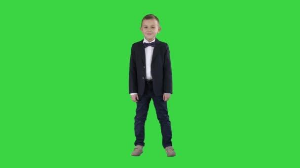 Mosolygó kisfiú formális ruhában állva egy zöld képernyő, chroma key.