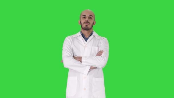 ernsthafter arabischer Arzt reifer Mann mit verschränkten Armen auf grünem Bildschirm, Chroma-Taste.
