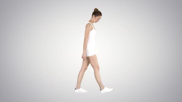 Mladá žena v sportovním oblečení procházka na pozadí s přechodem.