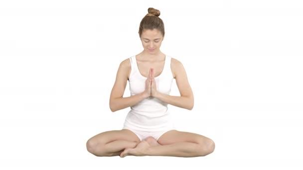 Charming yogi smiles and finishes the exercise on white background.