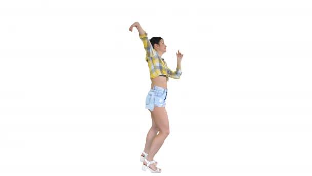wunderschöne süße Mädchen in Jeans Shorts, Turnschuhen, tanzen auf weißem Hintergrund.