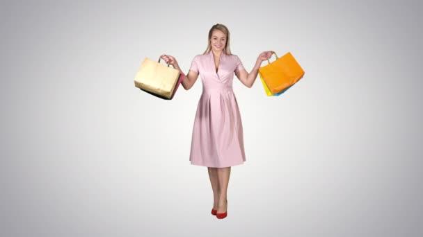 Mladá blondýnka v růžových šatech ukazující na nákupní tašky a procházky po přechodovém pozadí.