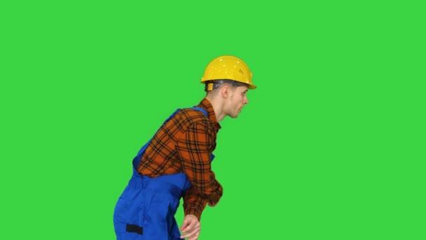 Irrer Tanz eines jungen Bauarbeiters in Schutzhut auf einem Green Screen, Chroma Key.