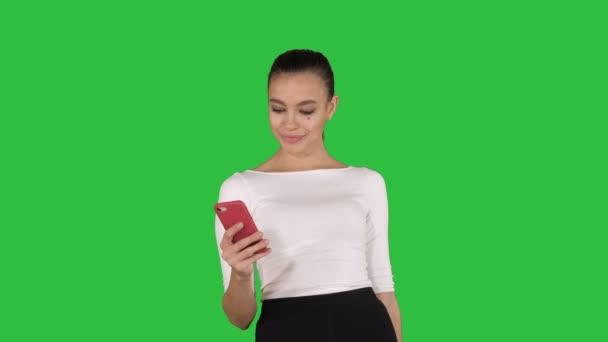 Krásná mladá žena používající mobilní telefon na zelené obrazovce, chroma klíč.