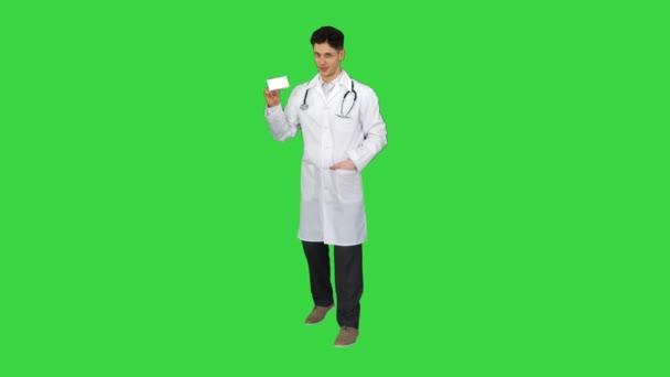 Lékař drží krabici pilulek, které je propagují a tančí na zelené obrazovce, Chroma Key.