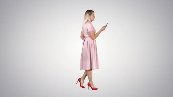 Žena v růžových šatech s telefonem na přechodovém pozadí.