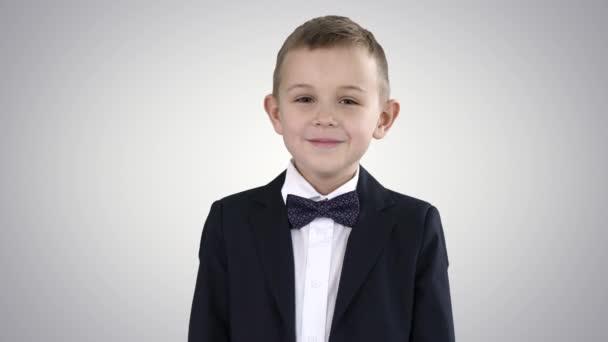 Mosolygó kisfiú formális ruhában állva gradiens háttér.