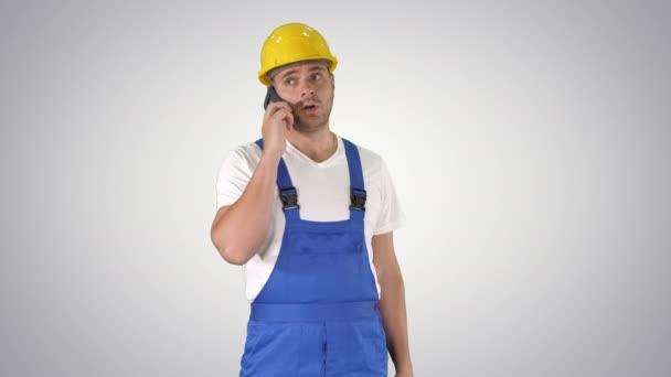 Stavební dělník na telefonu na gradientu pozadí.