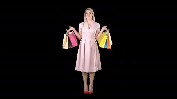 Woman with shopping bags in pink dress standing, Alpha Channel