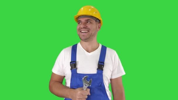 Přátelský konstruktor ochotný opravit něco ukázat palec na zelené obrazovce, chroma klíč.