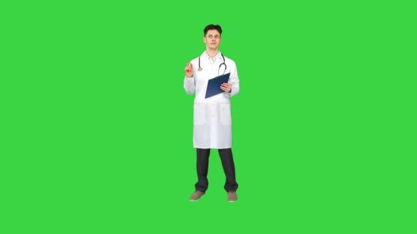 Arzt tanzt mit Tablet mit Dokumenten auf grünem Bildschirm, Chroma Key.