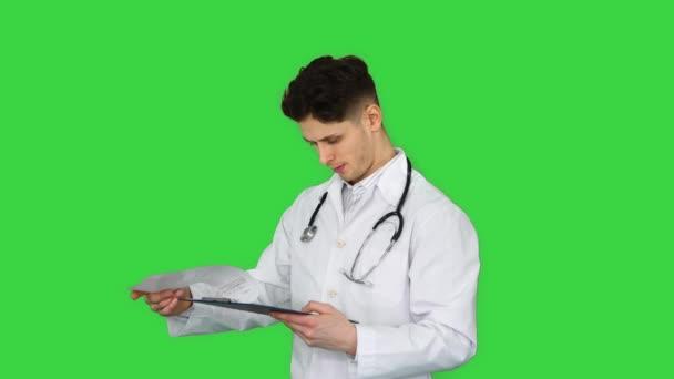 Wütender männlicher Arzt beim Betrachten von Dokumenten auf einem Green Screen, Chroma Key.