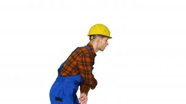 Funky tance mladého stavebního pracovníka z bezpečnostního klobouku na bílém pozadí.