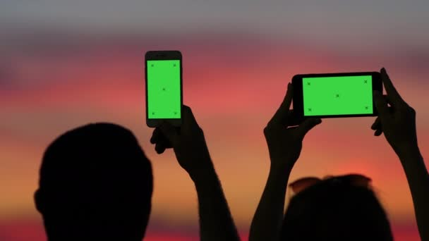ein Mann und eine Frau fotografieren den Sonnenuntergang mit ihren Handys, wir sehen sie von hinten.