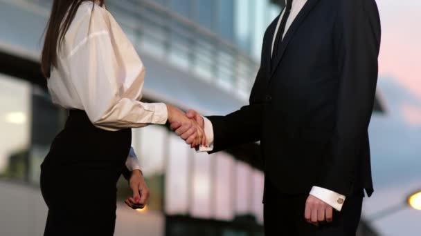 Podání ruky mezi obchodním člověkem a podnikatelskou ženou venku po podnikatelské stavbě.