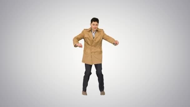 Junger Mann im Trenchcoat tanzt und amüsiert sich auf Steigungsuntergrund.
