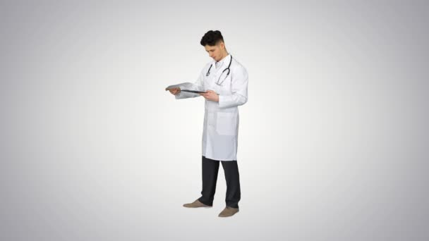 Angry male doctor looking at documents on gradient background.