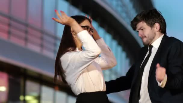 Joyful woman and man in business outfits dancing.