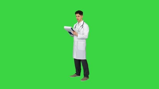 Tolle Ergebnisse Doktor Afler beim Durchsehen von Dokumenten auf einem Green Screen, Chroma Key.
