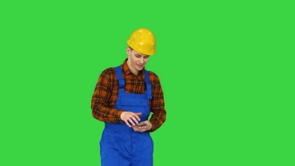 Builder counting his salary and dancing in a comic way on a Green Screen, Chroma Key.