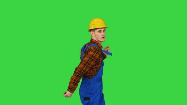Dancing young engineer with helmet after work on a Green Screen, Chroma Key.