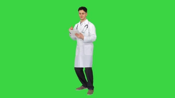 Attraktive selbstbewusste Ärztin, die mit Tablet tanzt, nachdem sie die Ergebnisse auf einem Green Screen gelesen hat, Chroma Key.