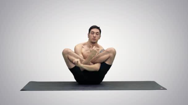 Muskulöser schöner junger Mann beim Training, Yoga, Lotus, Hände auf dem Gesicht auf Steigungshintergrund.