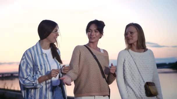 Három gyönyörű nő sétál és nevet a naplementében..