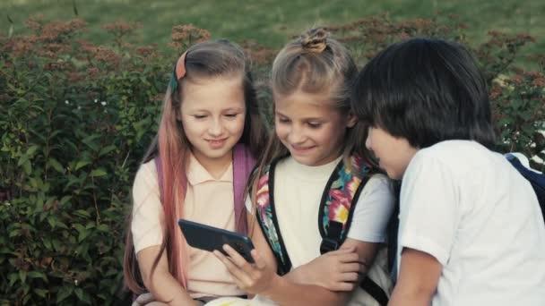 Boldog gyerekek élvezik a videót a telefonon.
