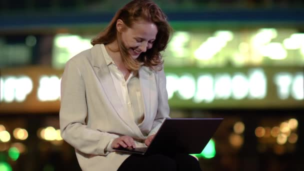Happy woman feeling excited looking at laptop screen outside in the evening.