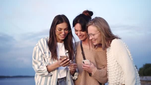 Jedna ženská ukazuje fotky nebo video svým přátelům. Všichni jsou pobavení.