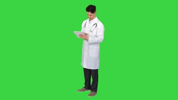 Doctor holding digital tablet pc and reading results on a Green Screen, Chroma Key.