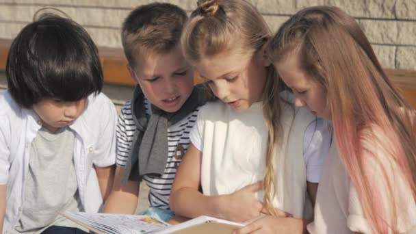 Roztomilé děti čtení knihy venku.