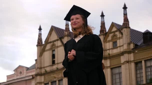Mosolygó diplomás lány a ballagási ceremóniát várva.
