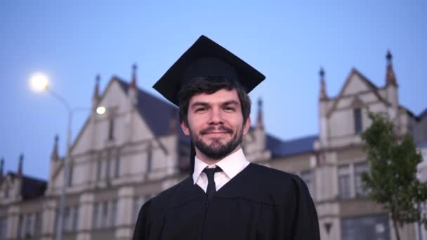 Vonzó mosolygós férfi diplomás állva és a kamerába nézve.
