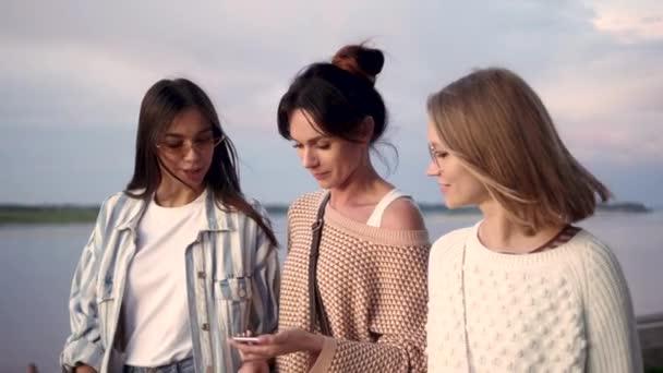 lässige Gruppe von Mädchen mit Smartphone-Spracherkennung beim Gehen.