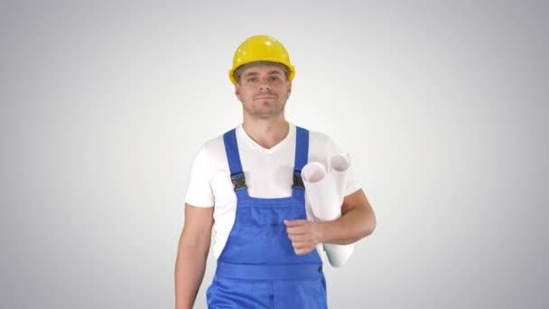 Stavební dělník kráčející s modrými tisky a s úsměvem na kameru na sklonu pozadí.
