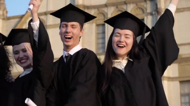 Graduating students smiling and laughing with diplomas.