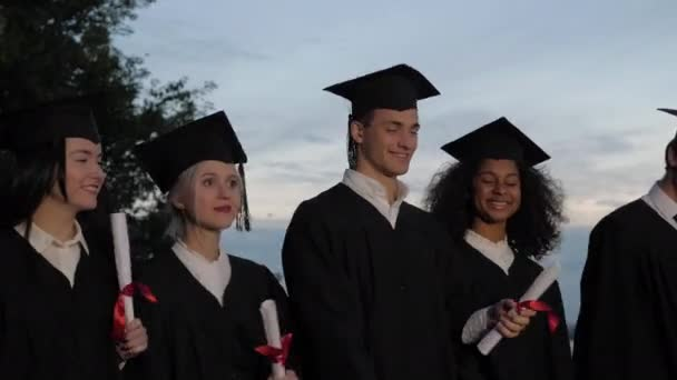 Happy smiled mixed races graduates walking with the diplomas in hands.
