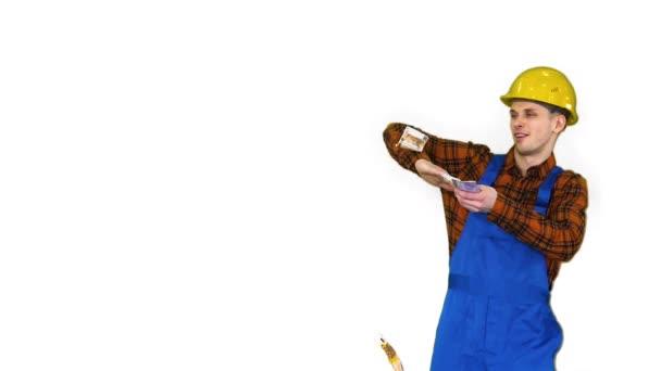 Bauarbeiter mit gelbem Hut wirft Geld auf weißem Hintergrund in die Luft.