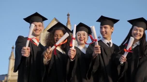 Usmívající se absolventi pózující v jedné řadě s diplomy.